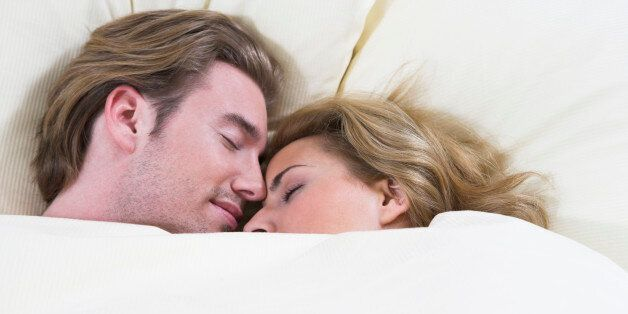 headshot of young couple sleeping closely together in