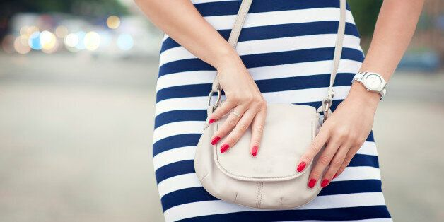 Fashionable woman with white bag in her hands and striped dress in the