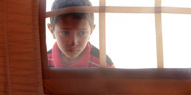 A Libyan child peers into the window of a tent in the U.A.E. Red Crescent refugee camp at the Tunisian...