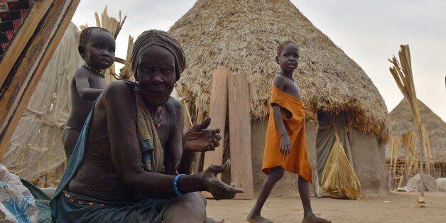 TO GO WITH AFP STORY BY AYMERIC VINCENOT An elderly woman sits on the ground outside a hut on one of...