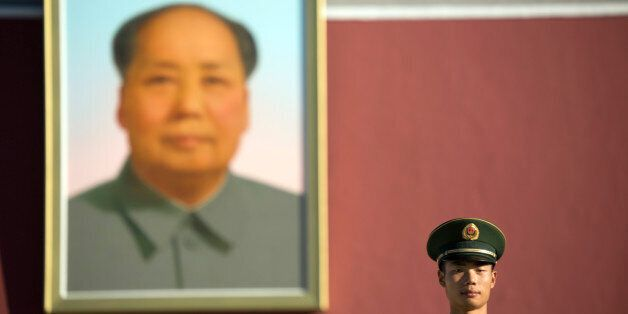 A Chinese guard stands on duty beneath the large portrait of former Chinese leader Mao Zedong on Tiananmen...