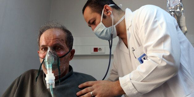 A Lebanese man, who suffers breathing problems caused by a sandstorm, breathes through an oxygen mask...