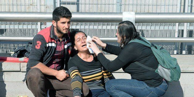 A woman is helped following an explosion at the main train station in Turkey's capital Ankara, on October...