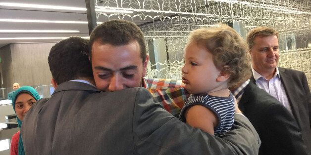 Egyptian Al-Jazeera English journalist Baher Mohammed, carrying his son Haroon, is welcomed by his colleagues...