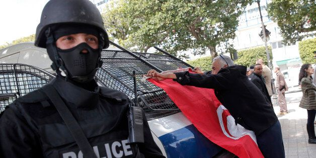 FILE - In this March 20, 2015 file photo, a man places a Tunisian flag onto a police car as a policeman...