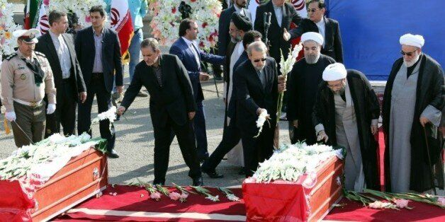 Le président iranien Hassan Rohani (c) et des officiels du gouvernement déposent des fleurs sur les cercueils...