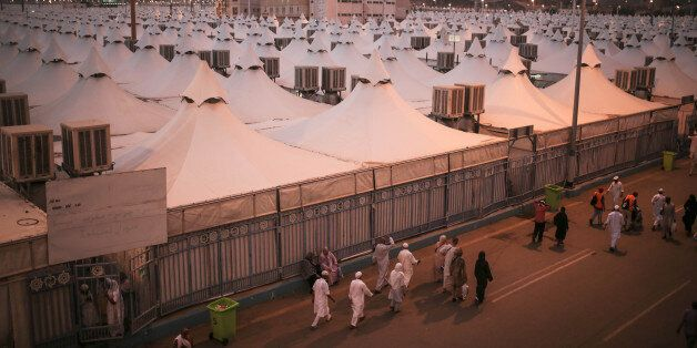 Muslim pilgrims walk past tents, a day after a stampede nearby killed more than 700 people, in Mina,...