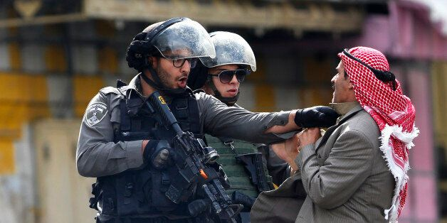 A Palestinian is pushed an Israeli policemen amid clashes in Hebron, West Bank, Saturday, Oct. 10, 2015....