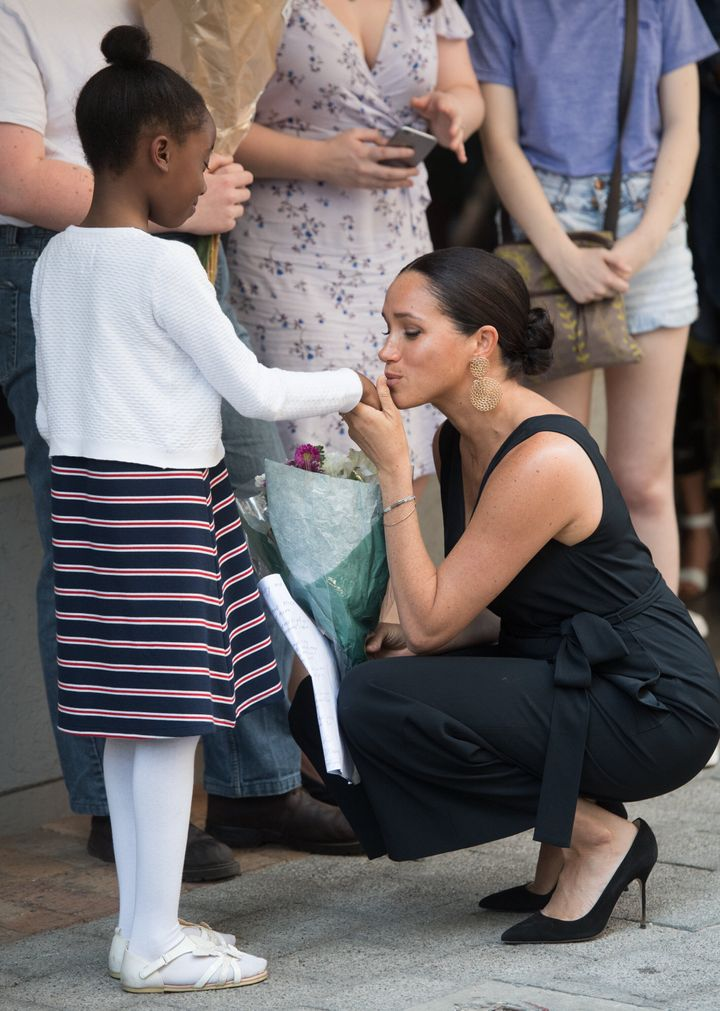 Meghan greeting a young girl at a mothers2mothers event.