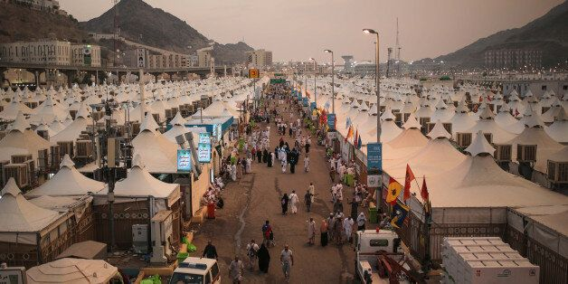 Muslim pilgrims walk past tents, a day after a stampede nearby in which more than 700 people died, in...