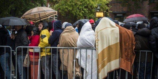 Des réfugiés font la queue devant le principal centre d'enregistrement des demandeurs d'asile à Berlin,...
