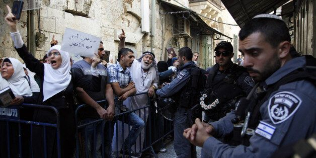 Israeli border police officers stand guard as Palestinians protest in the Old City of Jerusalem on Thursday,...