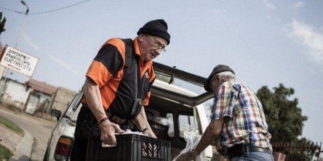 Adriaan Vlok (g), ancien ministre de l'apartheid, apporte de la nourriture au towsnhip d'Olievenhoutbosch,...