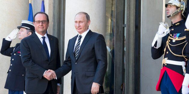French President Francois Hollande, left, greets his Russian counterpart Vladimir Putin upon his arrival...