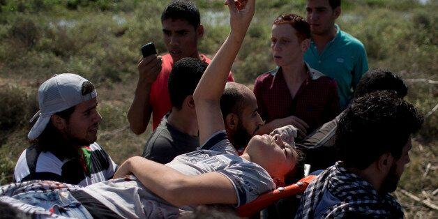 Palestinians carry a wounded man during clashes with Israeli soldiers on the Israeli border of Gaza City...