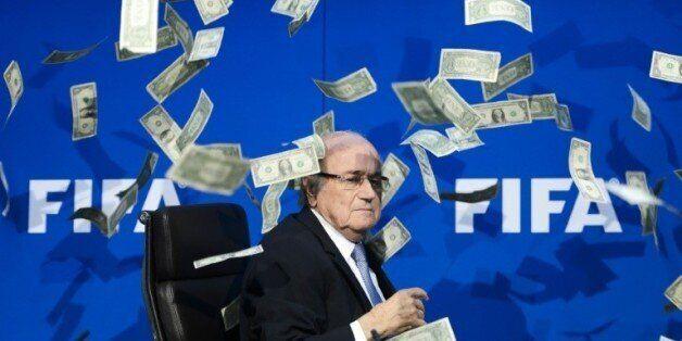 Le président démissionnaire de la Fifa Joseph Blatter reçoit des faux dollars lancés par un manifestant,...