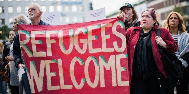 People hold a banner 'refugees welcome' as they take part in a demonstration in solidarity with refugees...