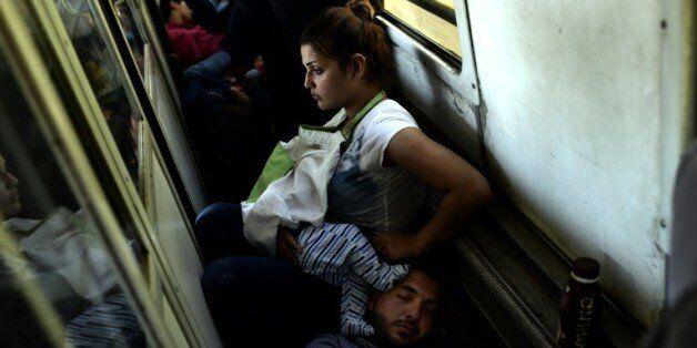 Des réfugiés irakiens Ahmad, Alia et leur bébé Adam voyagent, le 30 août 2015 dans un train de la Macédoine...