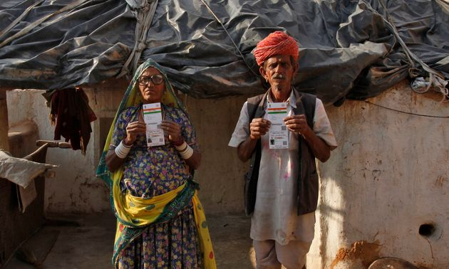 Ghewar Ram (R), 55, and his wife Champa Devi, 54, display their Unique Identification (UID) cards outside...