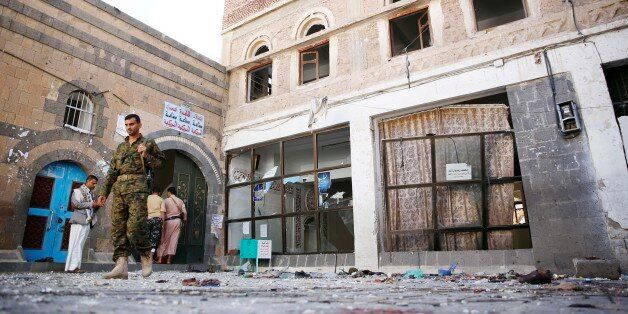 Shiite fighters, known as Houthis, inspect the the scene at the al-Balili mosque after two suicide bombings...