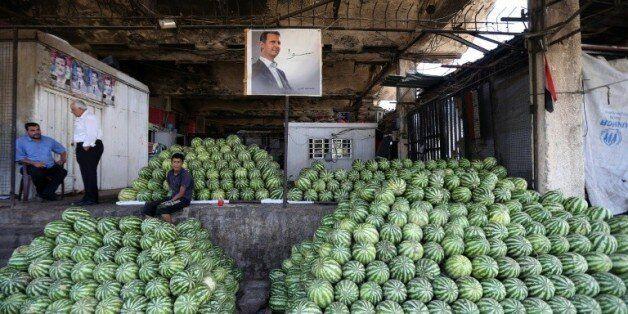 Des négociants syriens près du portrait du président Bachar al-Assad au marché des Halles de Damas, le...