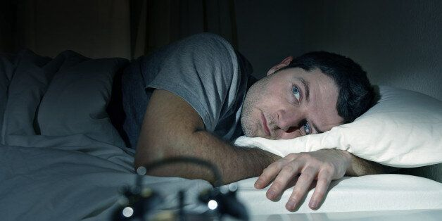 young man in bed with eyes wide opened suffering insomnia , stress and sleep disorder thinking about...