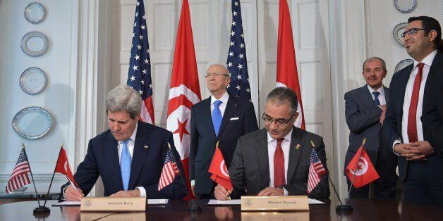 US Secretary of State John Kerry (L) and Tunisian Minister of Political Affairs Mohsen Marzouk (R) sign...