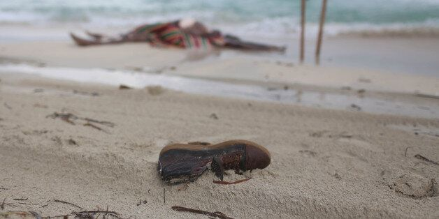 This Oct. 2, 2014 photo shows the clothes and shoes of migrants who washed up on the beach on the beach...