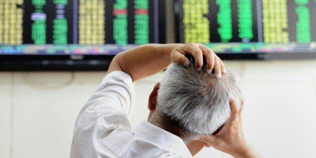 Un investisseur regarde les cotations chez un agent de change de Qingdao, dans la province de Shandong...