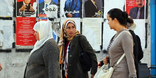 Tunisian women walk past a wall plastered with electoral campaign posters two days before the first round...