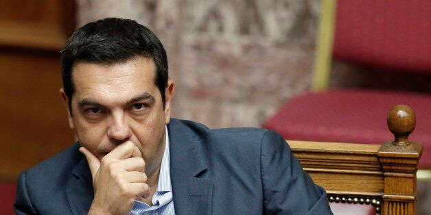 Greek Prime Minister Alexis Tsipras liestens during a parliamentary session in Athens, Friday, Aug. 14,...