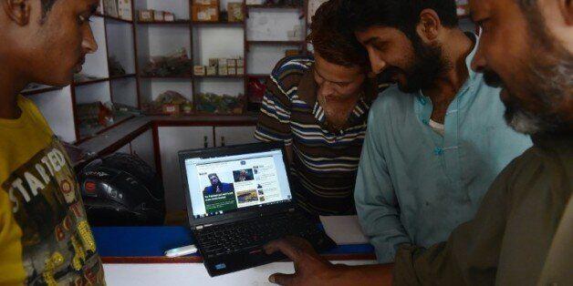 De jeunes Pakistanais surfent sur le site du Khabaristan Times dans une boutique à Rawalpindi, dans la...