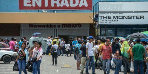 Des habitants font la queue à l'extérieur d'un supermarché de Valencia, à l'ouest de Caracas, le 11 août