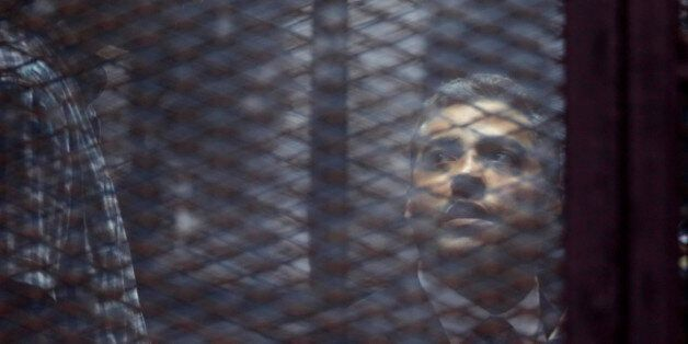 Canadian Al-Jazeera English journalist Mohammed Fahmy, listens to his verdict in a soundproof glass cage...