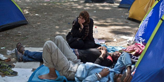 Migrants from Syria rest at a park in Belgrade, Serbia, Wednesday, Aug. 26, 2015. Thousands of migrants,...