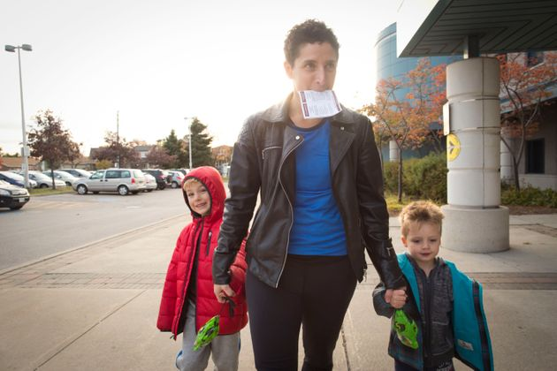 A mother goes to the polls with her two sons in Toronto, Oct. 19,