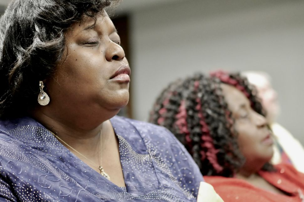 Activist Keisha Brown prays during a meeting at the Alabama Department of Environmental Management.