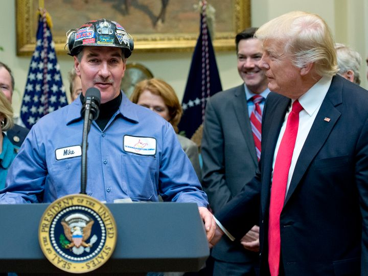 President Donald Trump gives the floor to a coal miner at the signing of a bill deregulating the industry. Warren's critics d