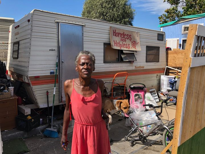 "Claudette Smith stands in front of her mobile home in an Oakland homeless encampment, with a sign that reads: ""Homeless not h"