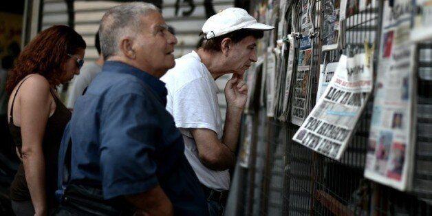 Des Grecs lisent les journaux du jour dans le centre d'Athènes, le 31 juillet