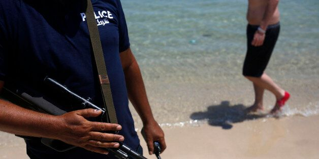 A Tunisian police officer guards the beach in front of the Imperial Marhaba Hotel in Sousse, Tunisia,...