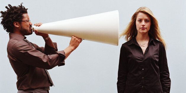 Man yelling into megaphone pointed at young woman's