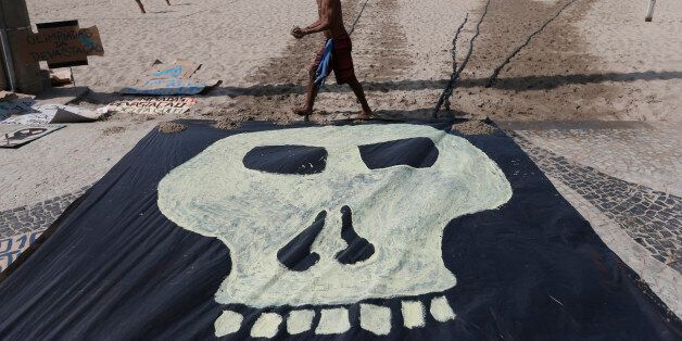 A man walks past a banner with a drawing of a skull symbolizing the death of nature during a protest...