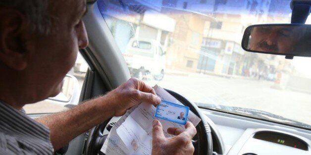 Un syrien montre son permis de conduire syrien lors d'un contrôle de la police syrienne à Hassaké dans...