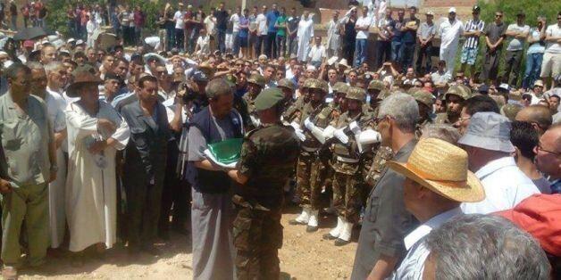 Un soldat remet l'emblème national au père du lieutenant Houssem Mâallem, lors l'enterrement à Tazougaghet,...