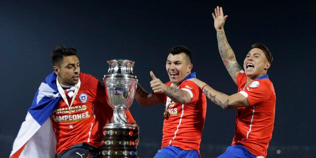 Chile's Gary Medel, center, and Chile's Eduardo Vargas, right, hold the trophy on top of the goal post...