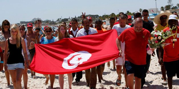 Tourists and residents, some displaying a Tunisian flag, walk on the beach to the scene of the attack...