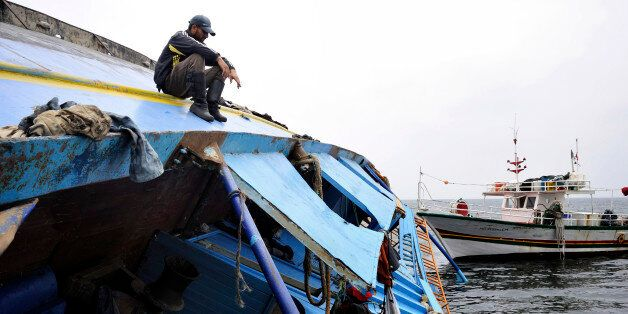 A Tunisian fisherman sits on a capsized ship that originated from Libya and which according to the United...