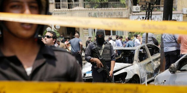 Egyptian security personnel stand guard after a bomb attack that targeted Egypt's prosecutor general...