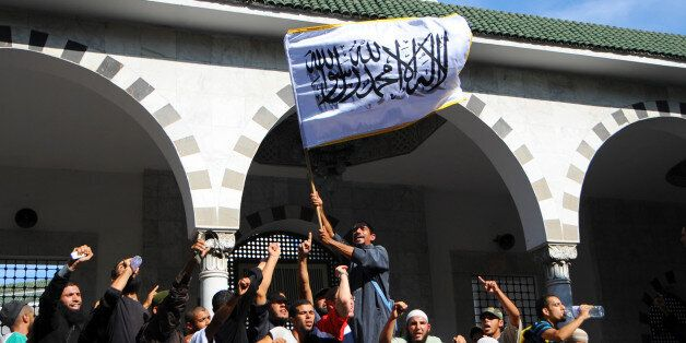 Tunisian activists stage a protest outside the El Fateh mosque surrounded by police, in support of a...